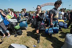 © Licensed to London News Pictures. 11/06/2015. Newport, UK.  Festival goers arrive at the Isle of Wight Festival 2015 carrying their tents and belongings just after being allowed onto the campsite at midday. This years festival include headline artists the Prodigy, Blur and Fleetwood Mac.  Photo credit : Richard Isaac/LNP