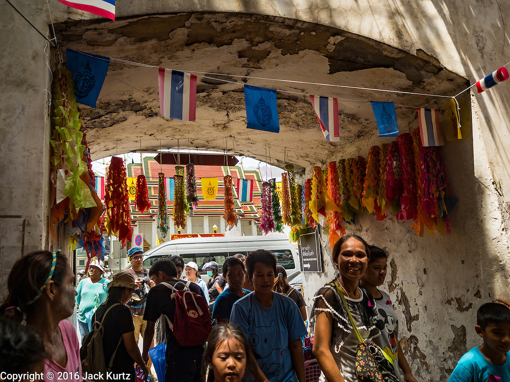 29 SEPTEMBER 2016 - BANGKOK, THAILAND:  People jam the entrance to the Pom Mahakan community, which is lined with Thai flags and paper flowers, a traditional Thai decorative garland. Forty-four families still live in the Pom Mahakan Fort community. The status of the remaining families is not clear. Bangkok officials are still trying to move them out of the fort and community leaders are barricading themselves in the fort. The residents of the historic fort are joined almost every day by community activists from around Bangkok who support their efforts to stay.    PHOTO BY JACK KURTZ