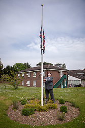 @Licensed to London News Pictures 08/05/2020. Maidstone, UK.. Former soldier from the 3rd Queens Regiment Gary Benson drops the Union Jack to half mast to pay tribute to VE75 Day at Queen Elizabeth Court in the Royal British Legion village in Aylesford, Kent. RBLI also wanted to use Two Minute Silence to honour the service and sacrifice of the Second World War generation and reflect on the devastating impact Covid-19 has had on so many lives across the world.  Photo credit: Manu Palomeque/LNP