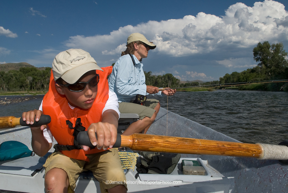 Ten-year-old Andy Nelson rows his mom, Barbara, down the South Fork of the Snake River (Idaho) while she fishes for trout from the back seat of the drift boat.