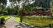 "The peaceful Byodo-In Temple reflects in a koi pond in Valley of the Temples Memorial Park, at 47-200 Kahekili Highway, Kaneohe, on the island of Oahu, Hawaii, USA. The Byodo-In Temple (""Temple of Equality"") was built in 1968 to commemorate the 100 year anniversary of the first Japanese immigrants to Hawaii. This Hawaii State Landmark is a non-practicing Buddhist temple which welcomes people of all faiths. The beautiful grounds at the foot of the Ko'olau Mountains include a large reflecting pond stocked with Japanese koi carp, meditation niches, and small waterfalls. Byodo-In Temple in O'ahu is a half-scale replica of the original Byodo-in Temple built in 1053 in Uji, Japan (a UNESCO World Heritage Site). This image was stitched from multiple overlapping images."
