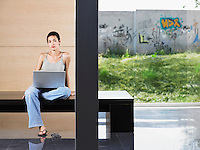 Young woman sitting down using laptop indoors portrait