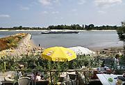 Nederland, Nijmegen, 19-8-2018 Door de aanhoudende droogte staat het water in de rijn, ijssel en waal extreem laag . Schepen moeten minder lading innemen om niet te diep te komen . Hierdoor is het drukker in de smallere vaargeul. Door uitblijven van regenval in het stroomgebied van de rijn komt het record, laagterecord in zicht . Veel mensen vermaken zich op het strand wat door het lage water ontstaan is. Uitzicht vanaf een terras op het water .Foto: Flip Franssen