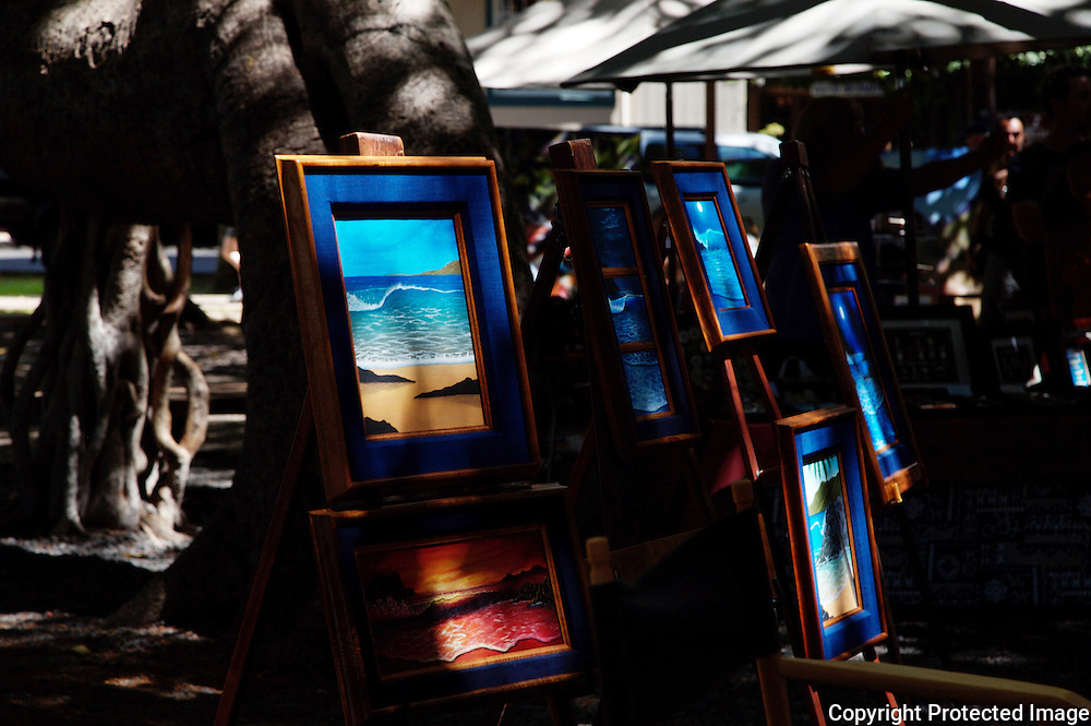 An Art Show in Lahaina, Maui catches afternoon light under a giant Banyan tree.