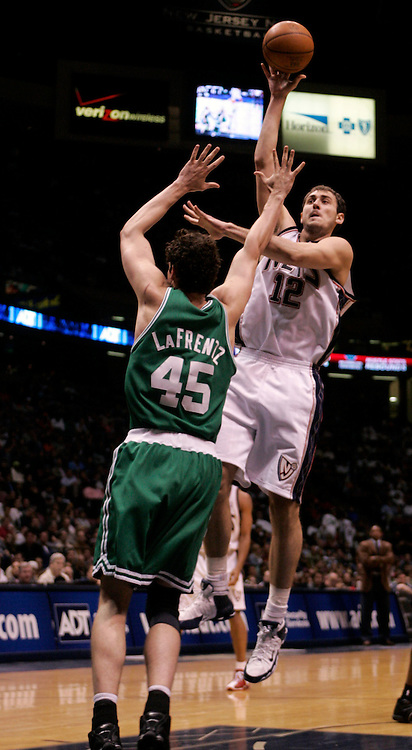 New Jersey Nets, Nenad Krstic  takes a shot over Boston Celtics, Raef LaFrentz  at The Continental Airlines Arena in East Rutherford New Jersey. Sunday 16 April 2006 (Andrew Gombert for the New York Times)