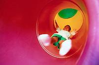 Boy Descending Tube Slide --- Image by © Jim Cummins/CORBIS