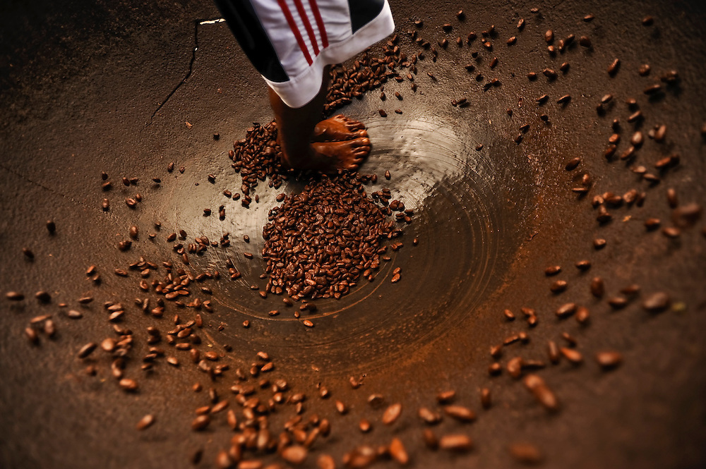 """Clinton Jean, 19, performs the """"cacao dance"""" for tourists from England at 18th-century Fond Doux Estate, a heritage tourism site, that has been operating cocoa tours and serving hearty Creole lunches for over a decade in St. Lucia. During the dance, Jean swung his feet around quickly in  circles, shining cocao beans with oil."""