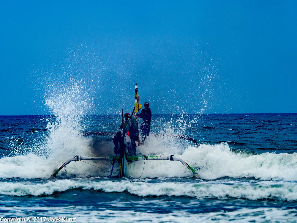 29 JULY 2017 - AIRKUNING, BALI, INDONESIA: An outrigger fishing canoe heads out to the Indian Ocean to lay fishing nets in Airkuning, a Muslim fishing village on the southwest corner of Bali. Villagers said their regular catch of fish has been diminishing for several years, and that are some mornings that they come back to shore with having caught any fish.    PHOTO BY JACK KURTZ