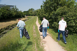 Men walking along River Leen picking up discarded rubbish,