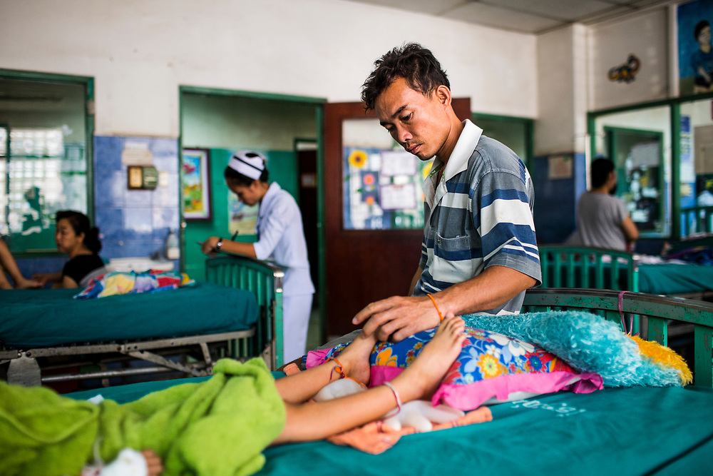 Namfon, aged 6, suffers from Japanese Encephalitis at a hospital in Vientiane, Laos. Her father Add watches over her all day and night at her bedside.