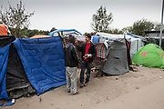 "Jack Steadman, who is taking a census of the camp talks to a refugee.  Photographed in ""The Jungle"" refugee camp in Calais France. Help Refugees UK has grown out of #helpcalais, a social media campaign started by Lliana Bird (Radio X DJ), Dawn O'Porter (Writer and Presenter), Josie Naughton and Heydon Prowse (The Revolution will be Televised) to raise a few funds and collect goods to take to Calais to help in some small way. The public response to the campaign was huge, and we were quickly able to provide aid in Calais and far beyond. Dani Lawrence' involvement begin when she filled a car with supplies and donations and drove to Calais."