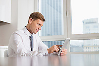 Mid adult businessman using digital tablet at kitchen table