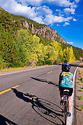 Cyclists passing the Rio Grande Palisades on Highway 149, Rio Grande National Forest, Colorado