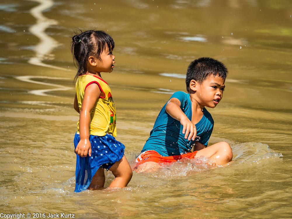30 SEPTEMBER 2016 - SAI NOI, AYUTTHAYA, THAILAND: Children play in floodwaters from the Chao Phraya River in Sai Noi. The Chao Phraya River, the largest river that runs through central Thailand, has hit flood stage in several areas in Ayutthaya and Ang Thong provinces. Villages along the river are flooded and farms are losing their crops due to the flood. This is the same area that was devastated by floods in 2011, but the floods this year are not expected to be as severe. The floods are being fed by water released from upstream dams. The water is being released to make room for heavy rains expected in October.      PHOTO BY JACK KURTZ