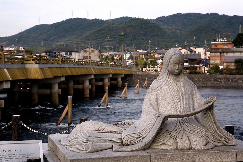 """Statue of Lady Murasaki who wrote """"The Tale of Genji 1000 years ago, now stands adjacent to the legendary Uji Bridge in Uji City south of Kyoto. The last 10 chapters of The Genji are set in and around what was then the wild and remote area of Uji, a popular retreat for the Heian Era aristocracy.."""