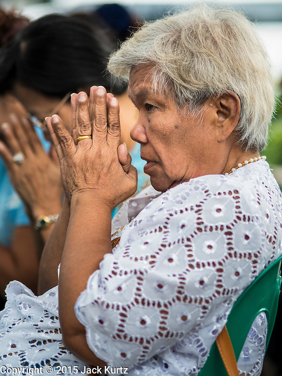 11 AUGUST 2015 - BANGKOK, THAILAND: A woman prays during a service to honor Queen Sirikit of Thailand before her 83rd birthday. Queen Sirikit was born Mom Rajawongse Sirikit Kitiyakara on August 12, 1932. She is the queen consort of Bhumibol Adulyadej, King (Rama IX) of Thailand. She met Bhumibol in Paris, where her father was the Thai ambassador. They married in 1950, she was appointed Queen Regent in 1956. The King and Queen had one son and three daughters. She has not made any public appearances since her hospitalization in 2012. Her birthday is celebrated as Mother's Day in Thailand, schools and temples across Thailand hold ceremonies to honor the Queen and mothers.      PHOTO BY JACK KURTZ