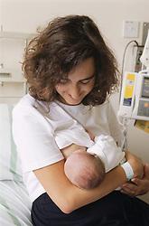 Mother breastfeeding new born baby on Maternity Unit in hospital,