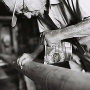 6/12/98-- EAST BOOTHBAY, Maine -- Roger F. Duncan of East Boothbay pours melted beeswax into the checks in his new schooner's foremast. The process is a method of sealing the wood, allowing it to absorb water in the summer when aboard and dry out in the winter while not allowing water i which might rot the interior.  This process need only be done once. Photo by Roger S. Duncan.