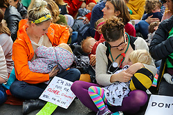 © Licensed to London News Pictures. 09/10/2019. London, UK. Campaigners from the Extinction Rebellion movement are seen breastfeeding as they take part in a mass nurse-in protest in Whitehall on day three of the two weeks protest. The activists are calling for the government to act on climate change. Photo credit: Dinendra Haria/LNP