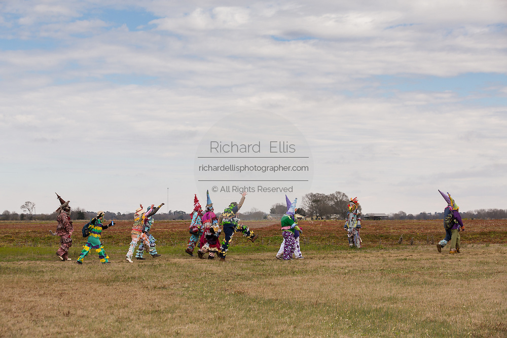 Costumed revelers walk across a farm field during the Faquetigue Courir de Mardi Gras chicken run on Fat Tuesday February 17, 2015 in Eunice, Louisiana. The traditional Cajun Mardi Gras involves costumed revelers competing to catch a live chicken as they move from house to house throughout the rural community.