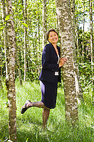 An Asian businesswoman in a lush green forest smiling while hugging a tree.