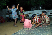 Rajasthani children dancing while watching a traditional television programme on a tv set in the couryard oftheir home (Rajasthan, India)