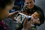 Alonso Rodriguez E-4 Specialist holds his twin daughters Alondra and Melanie Rodriguez 7-months old while their mother Karla Rodriguez takes a movie of them. More than 100 Sacramento-based members of the Guard's 2668th Transportation Company had a family get-together before they left for Iraq. PIcture taken at the National Guard Center on Meadowview Road, Tuesday, October 5, 2004.