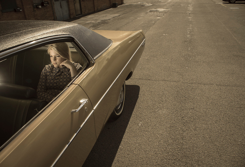 A 17-year-old Caucasian teenager wearing a blue, plaid, vintage dress, sits in the back seat of a 1972 Dodge Polara in a parking lot in Cortland, NY.
