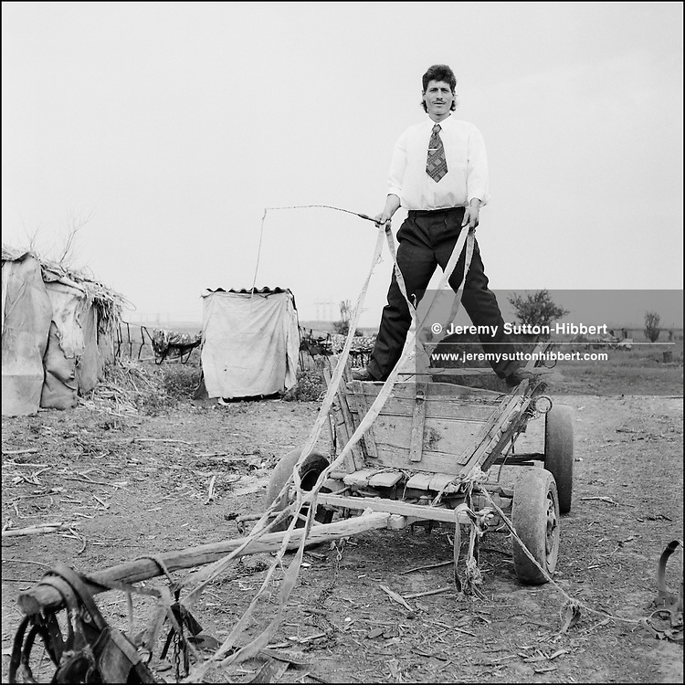 Posing for a portrait on top of a cart, a young Roma man in the Kalderash Roma camp of Sintesti, near Bucharest..
