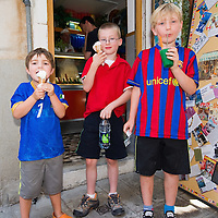 VENICE, ITALY - JUNE 30:   Three young customes enjoy an ice cream from Carlo Pistacchi's Gelateria Alaska in Santa Croce on June 30, 2011 in Venice, Italy. Carlo has been making ice-cream using fresh ingredients for more than 25 years and is renowned for experimenting with new flavours, offering his customers classic favourites such as rum and raisin or chocolate as well as some of his more unconventional creations such as asparagus or rocket salad and orange.