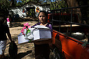 Vilma Yanet Ramos Argueta, 24, carries a coffin containing the human remains of Vilma Martinez Ramos, half-sister who she never met since she was killed during the La Joya massacre at the age of eleven months. The massacre at La Joya is one of six mass killings that took place in villages within the municipality of Meanguera from Dec. 11-13, 1981, by the US-trained Atlacatl Battalion of the Salvadorian Armed Forces, left over 900 civilian victims and are known collectively as the Massacre at El Mozote and surrounding villages. Earlier in 2016, an amnesty law signed after the 1992 Peace Accords that prevented war crimes from being investigated and tried was lifted by El Salvador's Supreme Court, allowing cases like El Mozote to proceed legally against its perpetrators. Jocoaitique, Morazan, El Salvador. December 11, 2016.