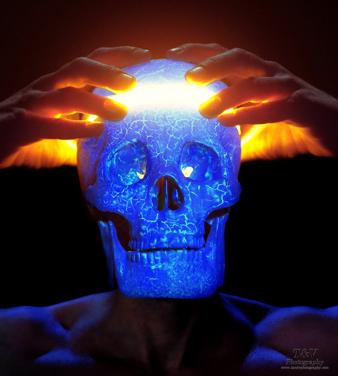 A glowing blue skull is split open to reveal a bright light by a pair of hands.Black light