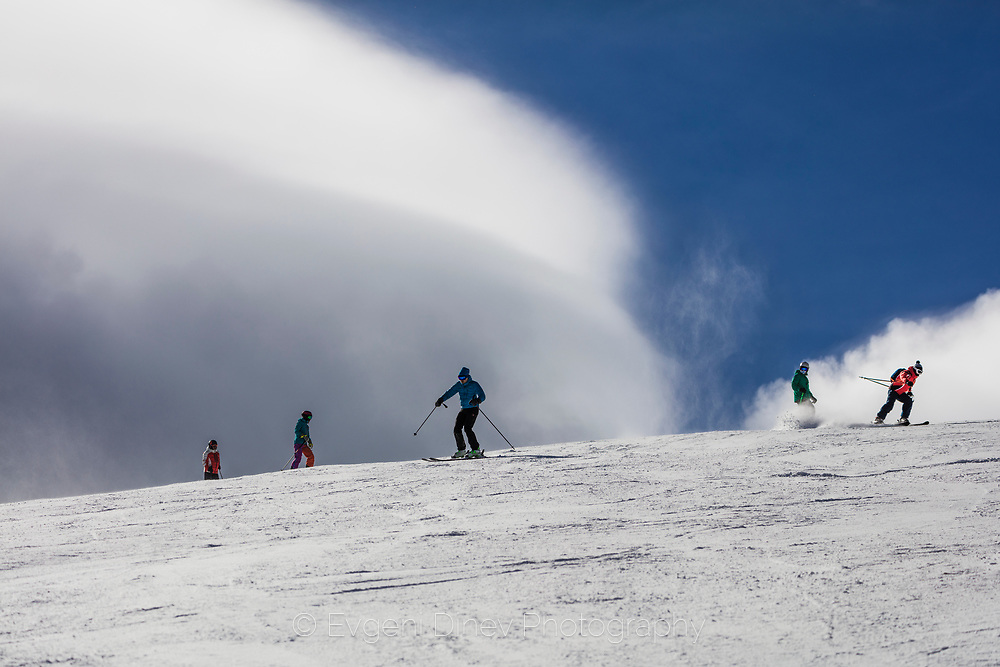 Skiers run down the ski slopes of Bansko ski area