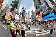 Times Square Alliance Safety officers near pedestrian striped crosswalk with tourists, electric billboards for broadway shows and businesses, a fisheye 180 degree view. NOTE: 180 degree view taken with fisheye lens (EDITORIAL USE ONLY)