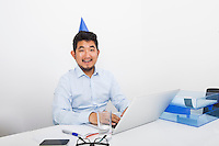 Portrait of happy businessman wearing party hat sitting at desk in office