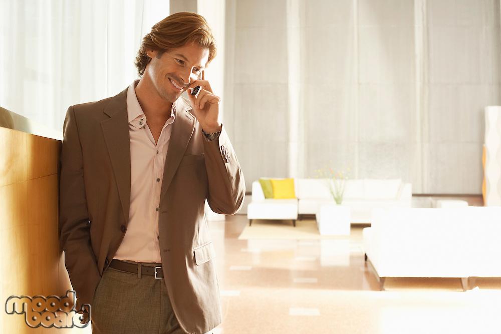 Businessman using mobile phone indoors