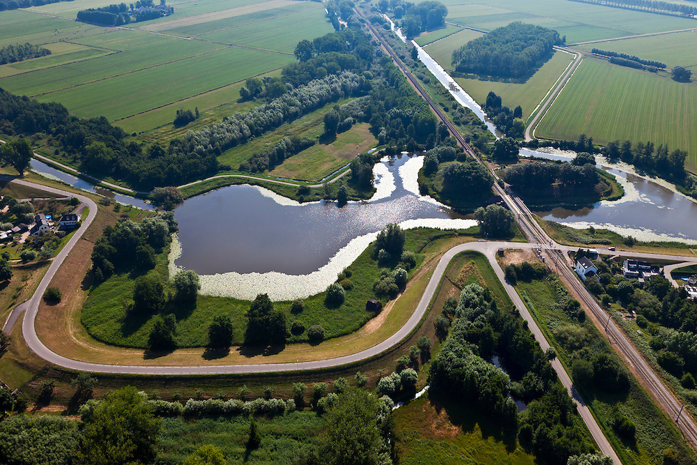 Nederland, Zuid-Holland, Gemeente Leerdam, 08-07-2010; Diefdijk met wiel, overblijfsel van een dijkdoorbraak. De dijk maakt onderdeel uit van Nieuwe Hollandse Waterlinie en omdat de dijk doorsneden wordt door de spoorlijn Leerdam-Geldermalsen is er een fort gebouwd (naam Werk op de spoorweg ). De Diefdijk is verder een binnendijk en oorspronkelijk aangelegd om de Alblasserwaard en de Vijfherenlanden tegen wateroverlast uit de Betuwe te beschermen. .Diefdijk with 'wheel', the remnants of a dike breach. The inner dike was originally built to protect the polders Alblasserwaard and Vijfherenlanden against flooding from the Betuwe. In addition, the dike is part of the New Dutch Waterline, hence the fortress which protects the 'breach' made by the railway..luchtfoto (toeslag), aerial photo (additional fee required).foto/photo Siebe Swart