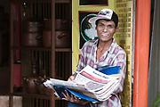 Young male selling newspaper beside the road in Yogyakarta.