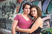 Sisters in a warm embrace with graffiti behind them in Graffiti Alley, Cambridge, Massachusetts, August 2018.