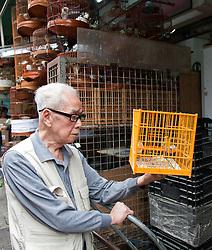Chinese man checks out a canary before buying. Bird Market, Hong Kong, China.