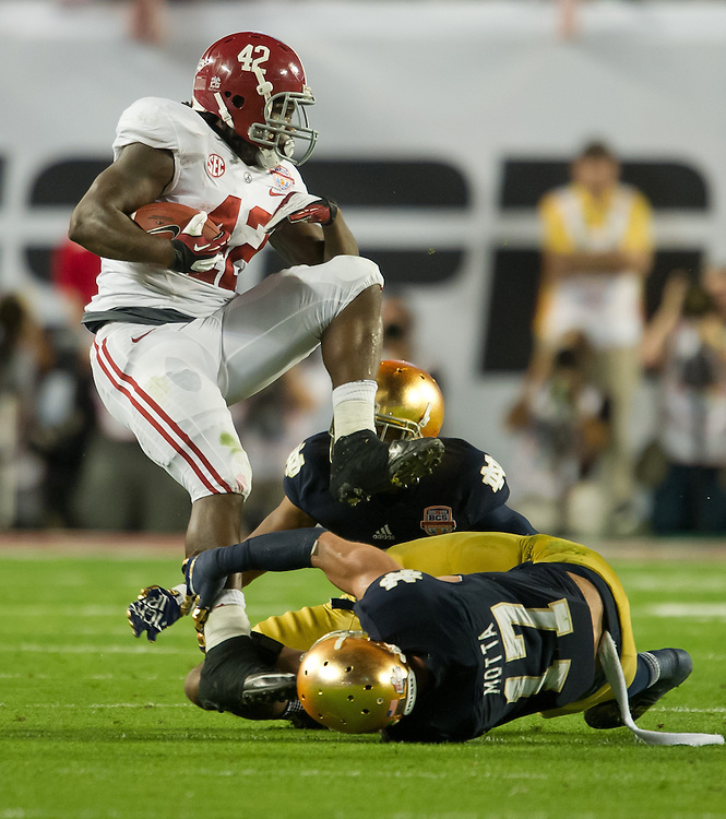 Alabama Crimson Tide running back Eddie Lacy (42) escapes the tackle attempt of safety Zeke Motta (17) in the first quarter.