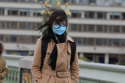 © Licensed to London News Pictures. 01/01/2020. London, UK. Windy weather in the capital as a woman wearing a surgical face mask walks on Westminster Bridge. Photo credit: Dinendra Haria/LNP