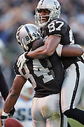 OAKLAND, CA - DECEMBER 19:  Wide receiver Jerry Porter #84 (caught 8 passes for 148 yards and 3 touchdowns) of the Oakland Raiders celebrates with teammate Alvis Whitted #87 after Porter caught a 3 yard touchdown pass in the third quarter for a 35-21 Raiders lead over the Tennessee Titans at Network Associates Coliseum on December 19, 2004 in Oakland, California. The Raiders defeated the Titans 40-35. ©Paul Anthony Spinelli *** Local Caption *** Jerry Porter;Alvis Whitted