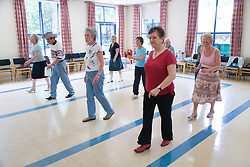 Group of women taking part in a line dancing lesson,