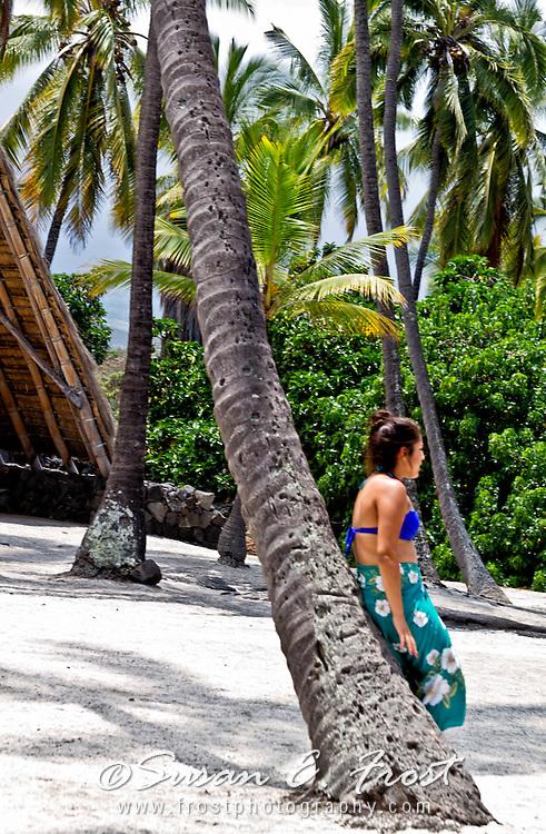 Woman leans against palm tree at Pu'uhonua o Honaunau, Place of Refuge, Big Island Hawaii.