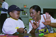 BOSTON, MA.Miss America Angela Perez Baraquio plays a counting game with Marquees O'Neal during a visit to the Cathedral Housing Development in the South End of Boston.