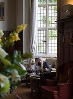 Senior man reading in interior with antique furniture