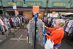 Woman browsing second hand clothes at Barras Market in Gallowgate Glasgow, United Kingdom