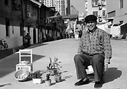 A pensioner suns some potted plants on a sunny sidewalk in Shanghai.