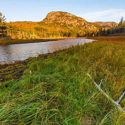 "Dune grasses and a tidal creek lead o ""the Beehive"" in Maine's Acadia National Park."
